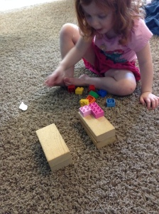 Abby thought the bridge building looked like fun, so she got in to build her own bridge to span the gap between blocks.