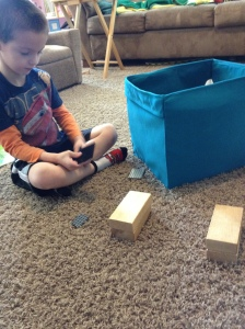 Nicholas was challenged to build a bridge between the two blocks that didn't touch the ground and could hold his cars. He managed it after a few false starts.